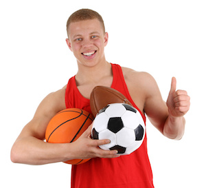 Guy holding different sports balls